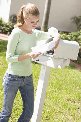 Young Woman Reading Letter at Mailbox